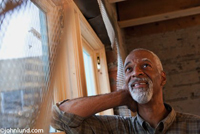 Black man, a contractor, leaning his elbow against a window sill in a new construction project. The senior black man has a gray goatee and close cropped gray hair. The man is looking up and smiling admiring his own work.